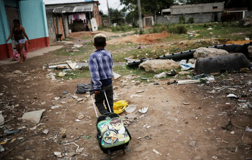 A boy pulls his school bag at a favela, or a slum, in Rio de Janeiro. Reuters