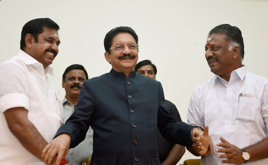 Tamil Nadu chief minister K Palaniswamy (L) greets O Panneerselvam (R) after he was sworn-in as the deputy chief minister in the presence of governor CH Vidyasagar Rao (C) at Raj Bhavan in Chennai on Monday. All India Anna Dravida Munnetra Kazhagam factions led by Palaniswamy and Panneerselvam formally merged on Monday afternoon. PTI