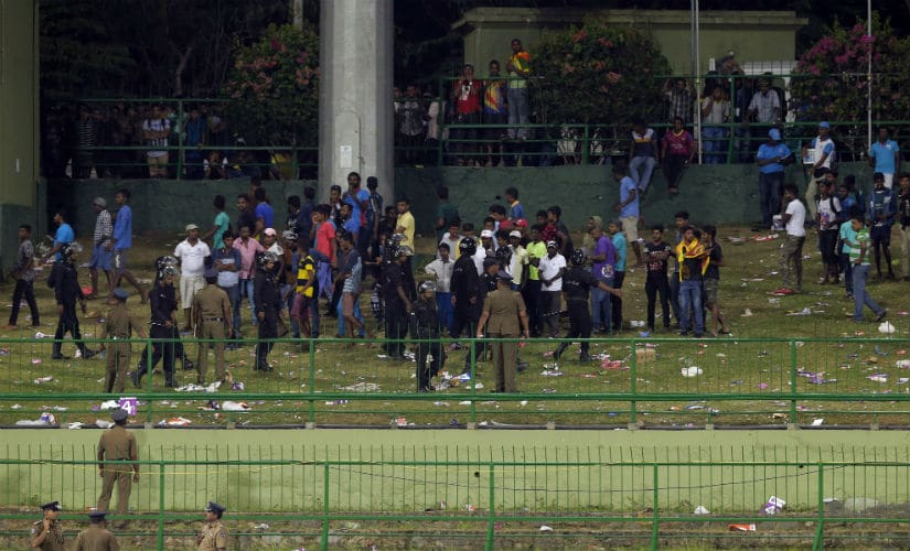 Sri Lankan police personnel ask people to leave after some spectators threw plastic bottles in the ground to disrupt the play between Sri Lanka and India in Pallekele. AP