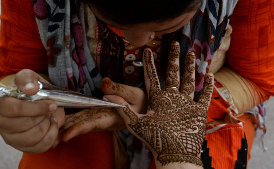 An Indian customer gets her hand is decorated with henna on the eve of the Rakhi festival in New Delhi. During the festival, sisters tie a sacred thread (rakhi) around their brothers wrists, and in return the brothers vow to protect their sisters. Getty images