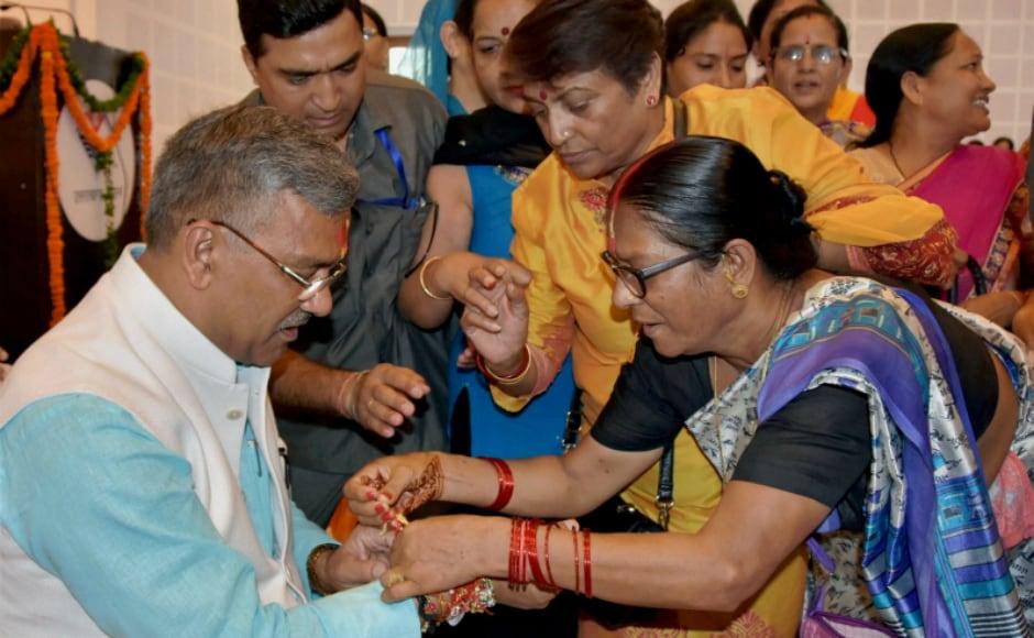 Women tie rakhi to Uttarakhand chief minister Trivendra Singh Rawat on the eve of Raksha Bandhan, in Dehradun. PTI
