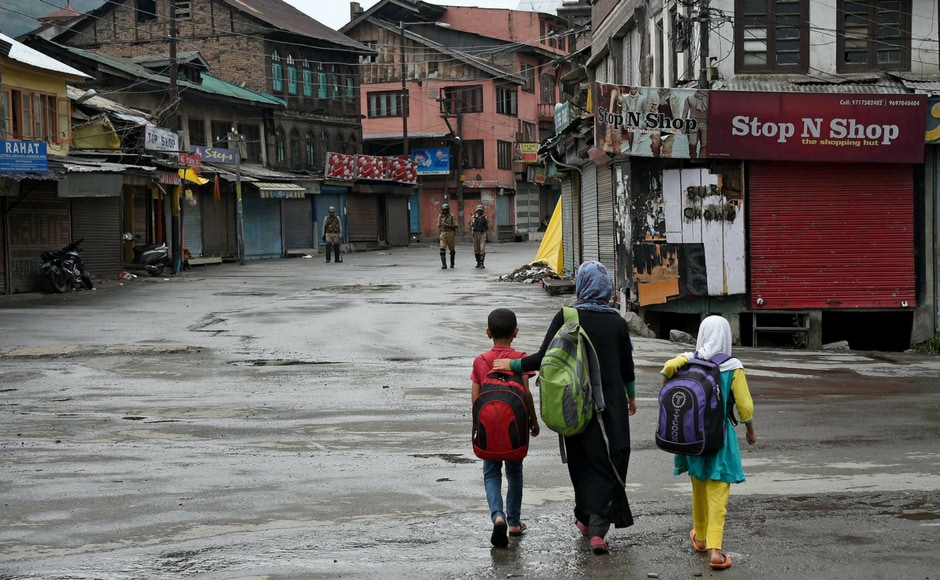 School children walk on a deserted street during restrictions and strike in Srinagar on Wednesday. Authorities imposed restrictions as the separatists called for a fresh strike following the killings of two top Lashkar-e-Toiba militants and a civilian in Pulwama. PTI