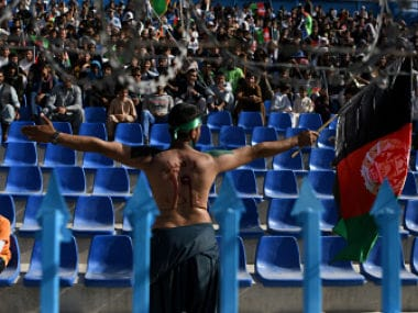 Afghan cricket fan waves the Afghan national flag with the name of Afghan's cricket sensation Rashid Khan painted on it during the Shpageeza Cricket League T20. AFP