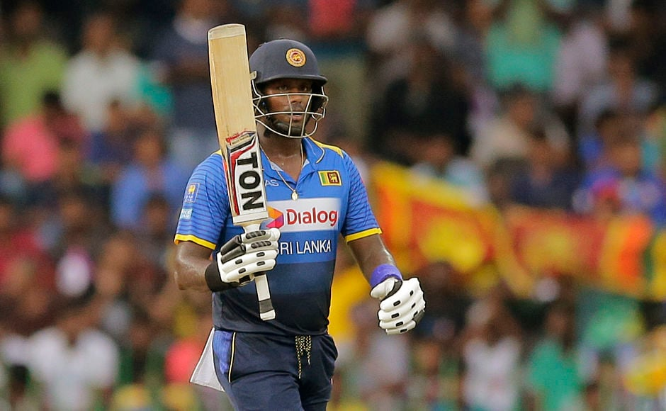 Sri Lanka's Angelo Mathews raises his bat to celebrate scoring fifty. He didn't stay long and was dismissed for 55 by Kuldeep Yadav. AP
