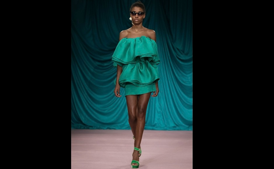 Another model stuns in an emerald green ensemble at the runway. Image from AP/Vianney Le Caer