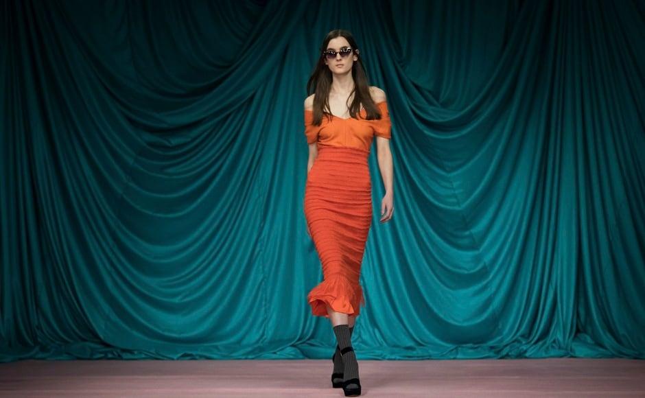 A model walks in an fiery orange dress by the designer at London Fashion Week. Image from AP/Vianney Le Caer