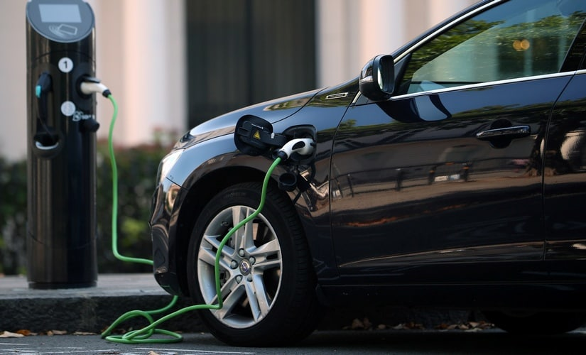 A hybrid electric car plugged in for charging
