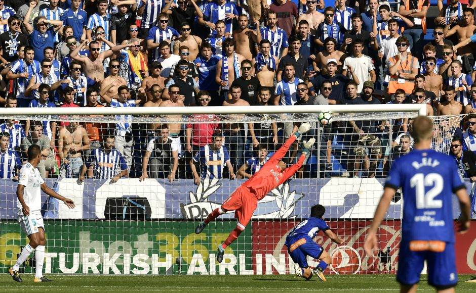 Alaves' Manu Garcia (bottom R) scores in front Real Madrid's goalkeeper Keylor Navas during the La Liga match.Garcia responded with Alaves' first goal of the season. AP