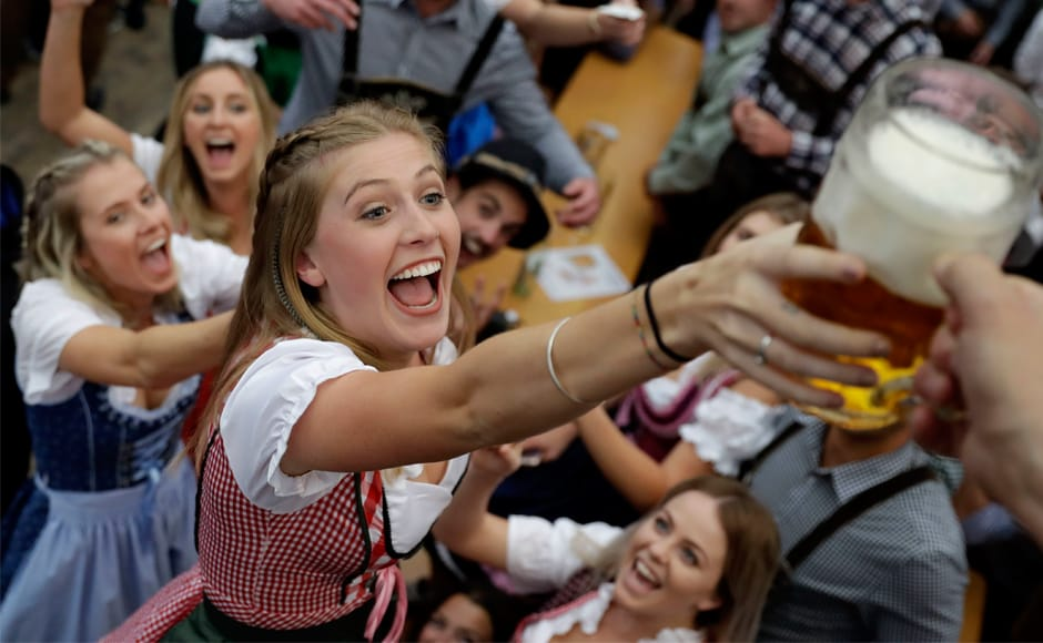 A young woman celebrates with more beer in Munich. About six million visitors are expected to throng Munich for the 184th Oktoberfest. AP