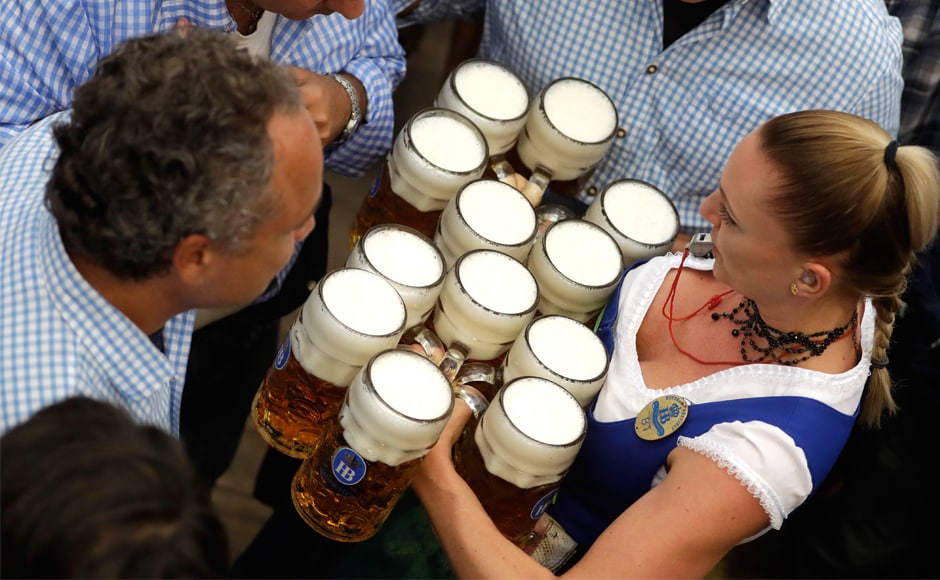 A waitress carries beer mugs through the crowd during the beer festival. Prices for a big mug of beer have gone up again, and visitors have to pay 10.95 euros (about $13) per glass — 25 cents more than last year. AP