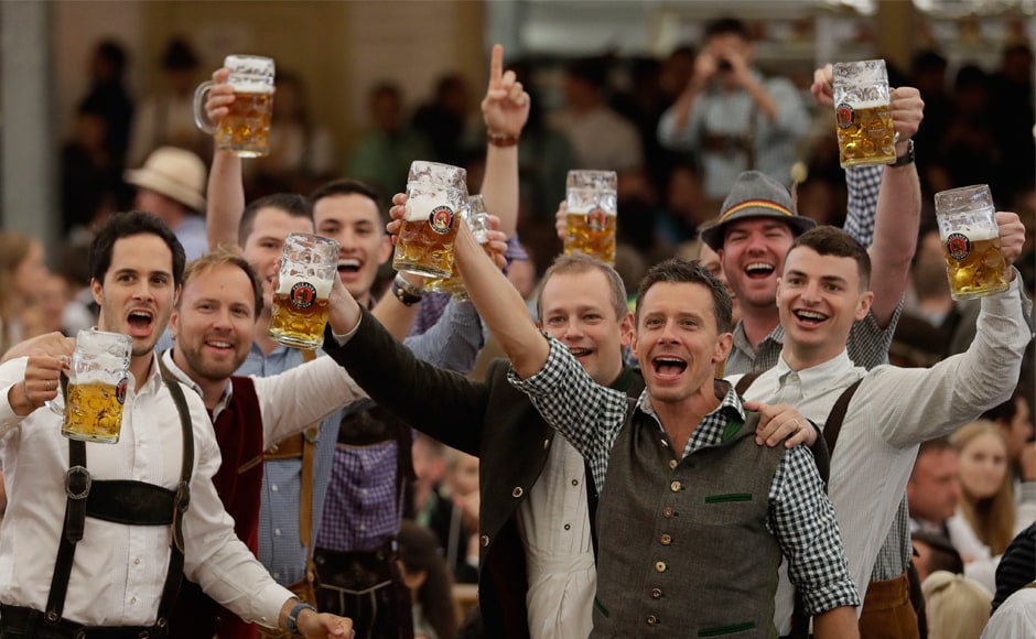 People celebrate at the beer festival in Munich. Crowds and bands often burst into <em>Ein Prosit der Gemütlichkeit</em>, a song considered the Oktoberfest anthem, which translates to 'A toast to cheer and good times'. AP
