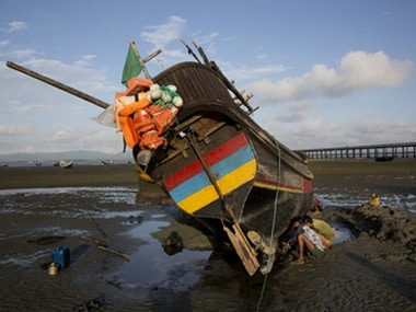 In this Sept. 21, 2017, local villagers repair a fishing boat in Shah Porir Dwip, an island by the Bay of Bengal at Bangladesh's southern tip. This island can mean both hope and death for the Rohingya Muslims who are desperate to escape the violence that has engulfed their lives in Myanmar's Rakhine state. AP