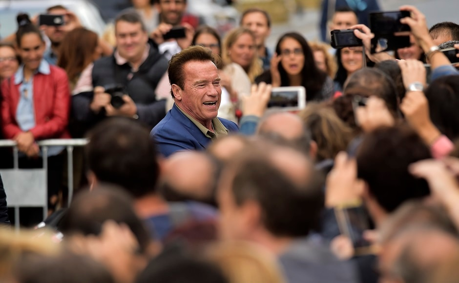 Arnold Schwarzenegger greets fans as he arrives to promote the film Wonders Of The Sea. Image from AP