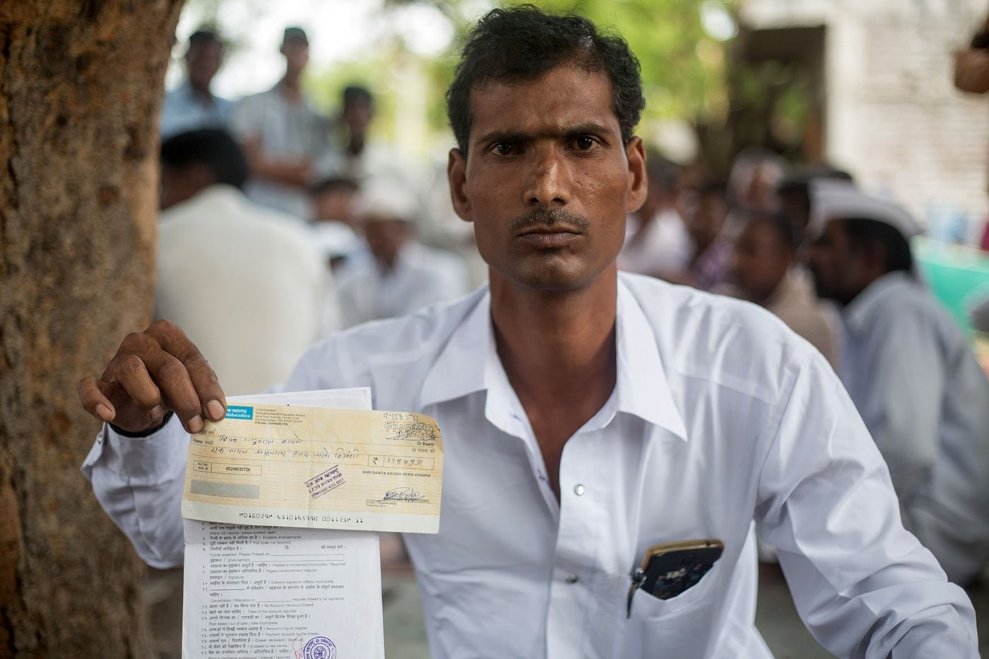 Deepak Badavne holds up the cheque he received in return for his cotton – it bounced three times. Image courtesy: Shrirang Swarge