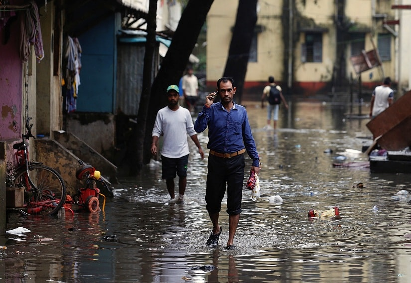 People walk through a partially flooded street at a residential area in Mumbai, India, August 30, 2017. REUTERS