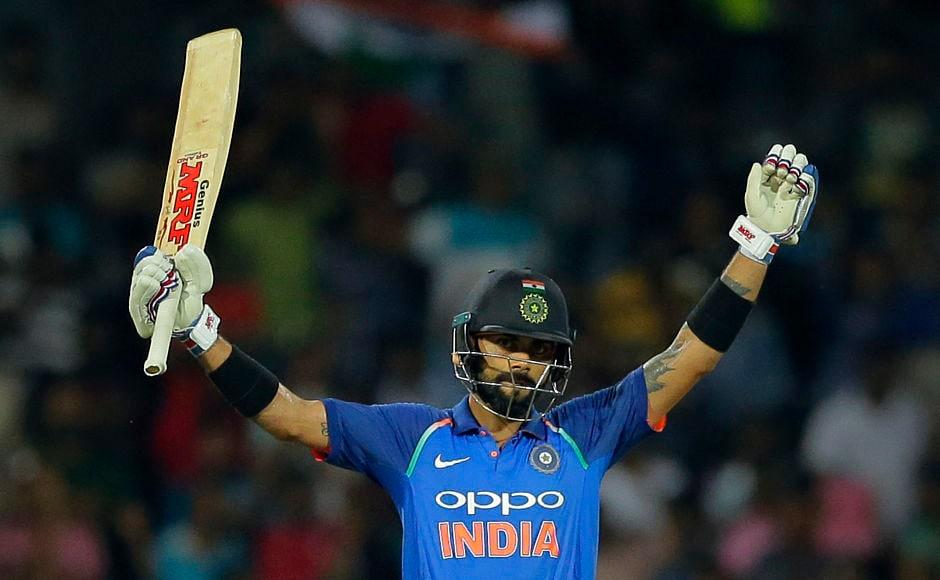 India's captain Virat Kohli raises his bat to celebrate scoring his 30th century. AP