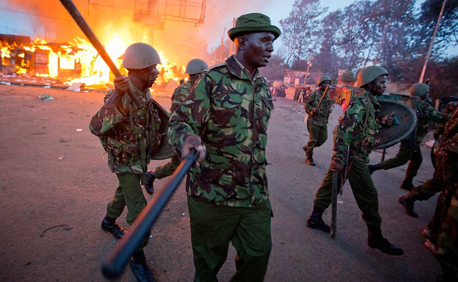 At least six people have died in violence linked to the latest election, including a man who was shot and killed in the Nairobi slum of Kawangware as security forces moved to quell fighting between gangs from different ethnic groups late Friday. Police move past burning shops during clashes in Nairobi. AP