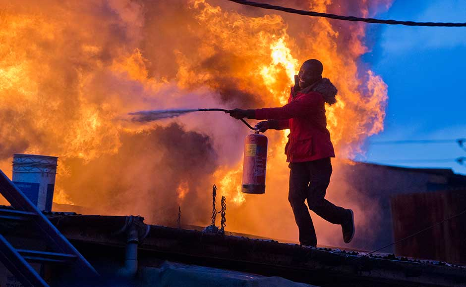 The election commission has asked Kenyans to be calm and patient while it counts and verifies results from the new vote. A man tries to extinguish the fire set during clashes in Nairobi. AP