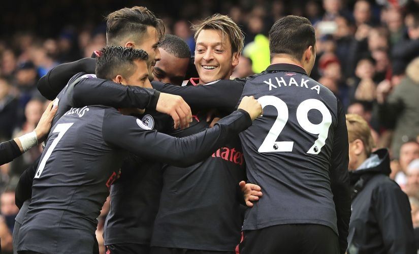 Arsenal's Mesut Ozil, center, celebrates scoring his side's second goal against Everton. AP