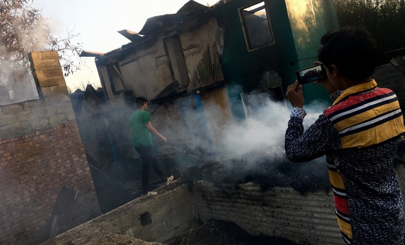 A child takes pictures of burnt house of Mohammad Ramzan Sheikh. A steel trunk, few half-burnt clothes and some charred utensils is all that remains of Sheikh's house. Sameer Yasir/Firstpost