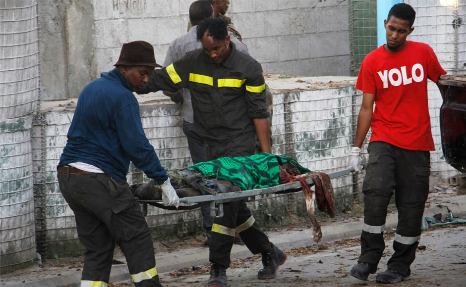A dead body is carried in Mogadishu. Security officials say the bomber had pretended that his truck had broken down outside the hotel gate. The bomber stopped outside the heavily fortified hotel and pretended to repair the truck before finally turning it around and detonating. AP