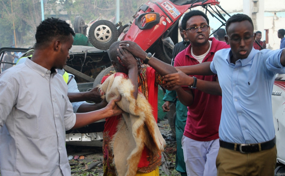 Somalis help a man injured in the blast. Saturday's blasts came two weeks after more than 350 people were killed in a massive truck bombing on a busy Mogadishu street, in the country's worst-ever attack. AP