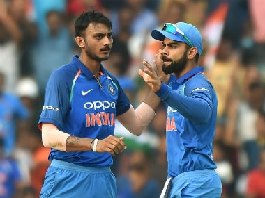 India's Axar Patel (L) celebrates with captain Virat Kohli after taking the wicket of Australia's Travis Head during the 5th ODI in Nagpur. AFP