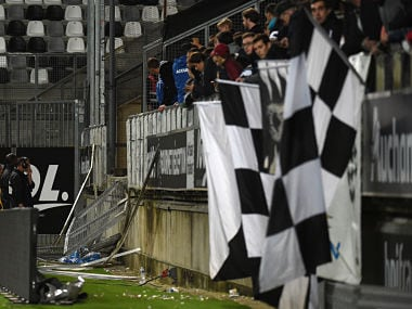 Members of the stadium staff stand by the stadium barrier that collapsed during the French L1 football match between Amiens and Lille LOSC on September 30, 2017 at the Licorne stadium in Amiens. Several Lille supporters were hurt in Amiens when a stadium barrier collapsed in the away section as the visiting fans celebrated the opening goal of the match. The Ligue 1 fixture was interrupted in the 16th minute after LOSC French defender Fode Ballo-Toure's goal sparked celebrations that caused a fence separating the fans from the pitch to crumble under their weight. / AFP PHOTO / FRANCOIS LO PRESTI