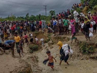 Rohingya Muslims, who crossed over from Myanmar into Bangladesh, walk through muddy field. AP
