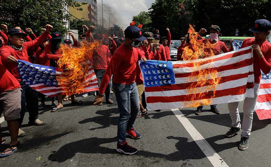 """Carrying placards declaring """"Dump Trump"""" and """"Down with US Imperialism"""", the left-wing protesters were blocked by police in riot gear with shields and batons, and were then showered with jets of water from a fire engine. Protesters burnt mock US flags during a rally near the venue of ASEAN summit and meetings in Manila. AP"""