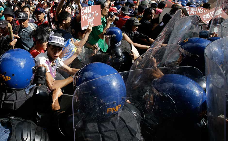 """The Philippines will be Trump's last stop on a marathon tour across Asia. Despite Trump's """"America First"""" policy, the visit should provide some reassurance that Washington remains committed to a region that Beijing sees as its strategic domain. Protesters scuffle with police as they are dispersed while trying to get near the US Embassy in Manila. AP"""