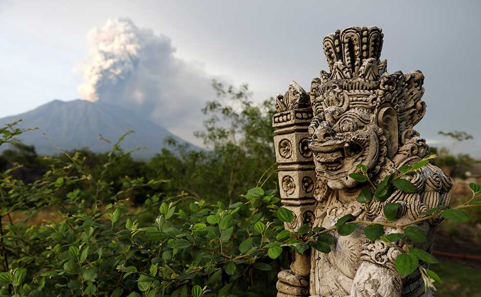 On Tuesday, life was going on largely as normal in villages surrounding Agung, with residents offering prayers as the volcano sent columns of ash and smoke into the sky. A statue on a bridge is seen as Mount Agung volcano erupts in the background. Reuters