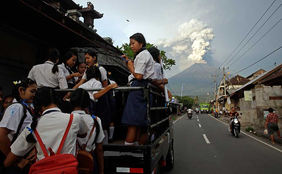 While the population in the area has been estimated at between 63,000 and 1,40,000, just over 29,000 people were registered at emergency centres, said Sutopo Purwo Nugroho, a spokesman for the Disaster Mitigation Agency. School students stand on a truck as their transport to go to school with the Mount Agung volcano spews smoke and ash. AP