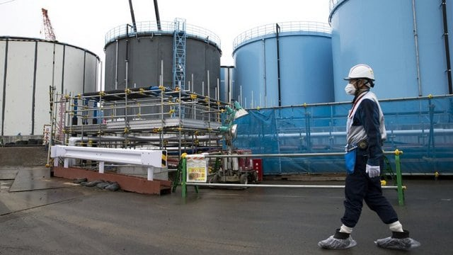 An employee walks past storage tanks for contaminated water at the tsunami-crippled Fukushima Dai-ichi nuclear power plant of the Tokyo Electric Power Co. (TEPCO). Image: AP