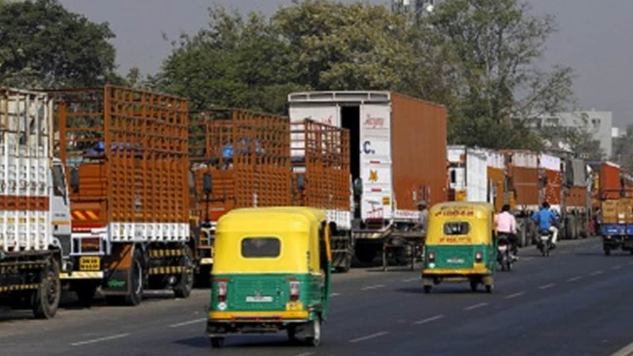 Auto rickshaws move past parked trucks along a national highway on the outskirts of Ahmedabad, India, December 2, 2015. India will force all commercial trucks more than 15 years old off the road from April and is reviewing how it checks vehicle emissions, a senior transport official said, as the government tries to curb soaring urban air pollution. Picture taken December 2. REUTERS/Amit Dave - RTX1WWMQ