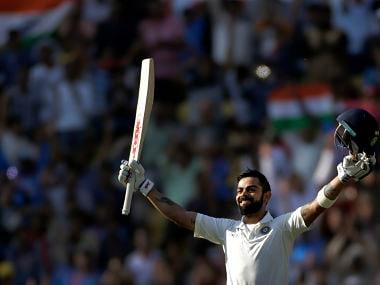 India's captain Virat Kohli raises his bat and helmet to celebrate scoring double century during the third day of their second test cricket match against Sri Lanka in Nagpur, India, Sunday, Nov. 26, 2017. (AP Photo/Rajanish Kakade)