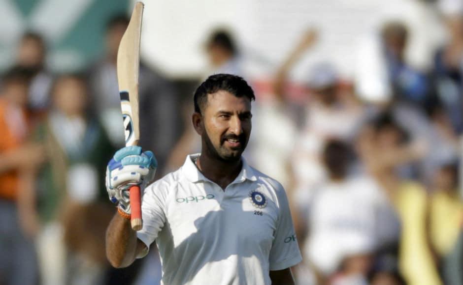 Cheteshwar Pujara raises his bat after completing his 14th Test century. AP