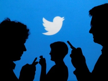 People holding mobile phones are silhouetted against a backdrop projected with the Twitter logo. Reuters