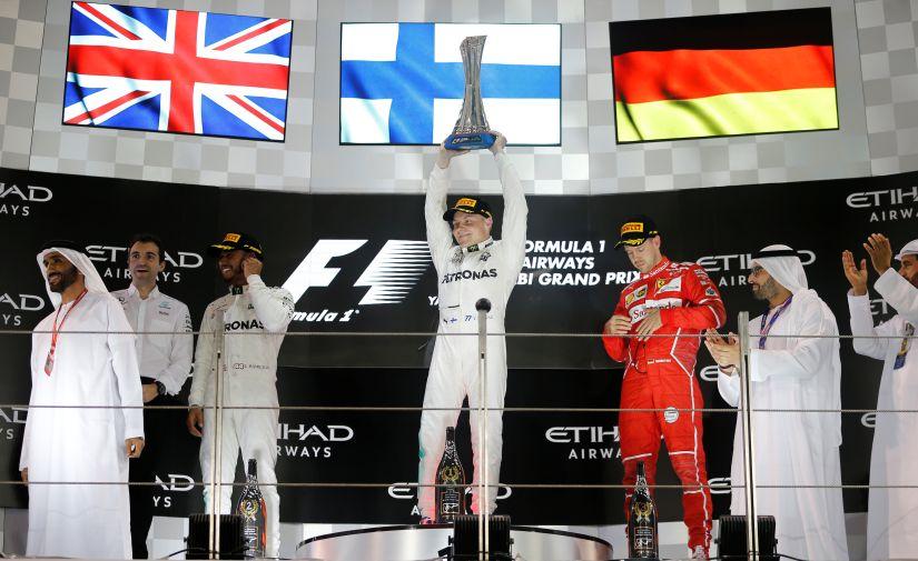 Mercedes' Valtteri Bottas celebrates with the trophy after winning the Abu Dhabi Grand Prix as Mercedes' Lewis Hamilton and Ferrari's Sebastian Vettel look on. Reuters