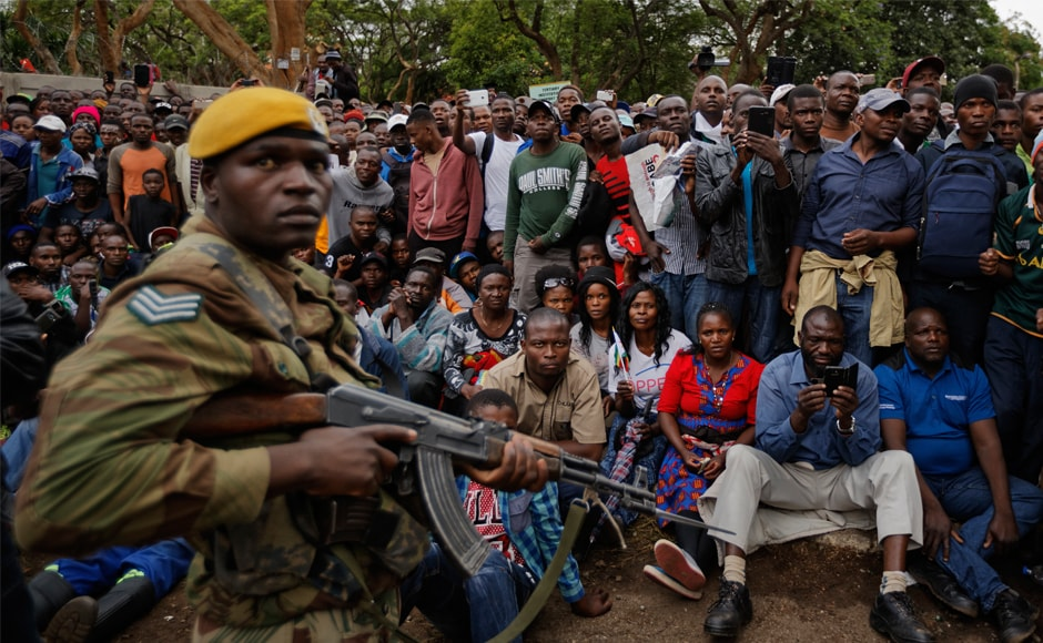An army soldier stands guard of the crowd. Mugabe, the only ruler Zimbabwe has known since independence from Britain in 1980, has been holed up in his lavish 'Blue Roof' compound, from where he has watched support from his Zanu-PF party, the security services and the people evaporate in the wake of a military seizure of power on Wednesday. AP