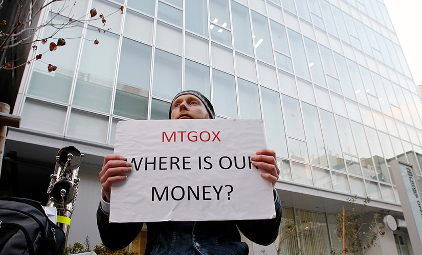 Kolin Burges, a self-styled cryptocurrency trader and former software engineer who came from London, holds a placard to protest against Mt. Gox, in front of the building where the digital marketplace operator is housed in Tokyo February 25, 2014. The website of Mt. Gox appears to be taken down, shortly after six major Bitcoin exchanges released a joint statement distancing themselves from the troubled Tokyo-based bitcoin exchange. Tokyo-based Mt. Gox was a founding member and one of the three elected industry representatives on the board of the Bitcoin Foundation. REUTERS/Toru Hanai (JAPAN - Tags: BUSINESS CIVIL UNREST SCIENCE TECHNOLOGY) - GM1EA2P1CT001