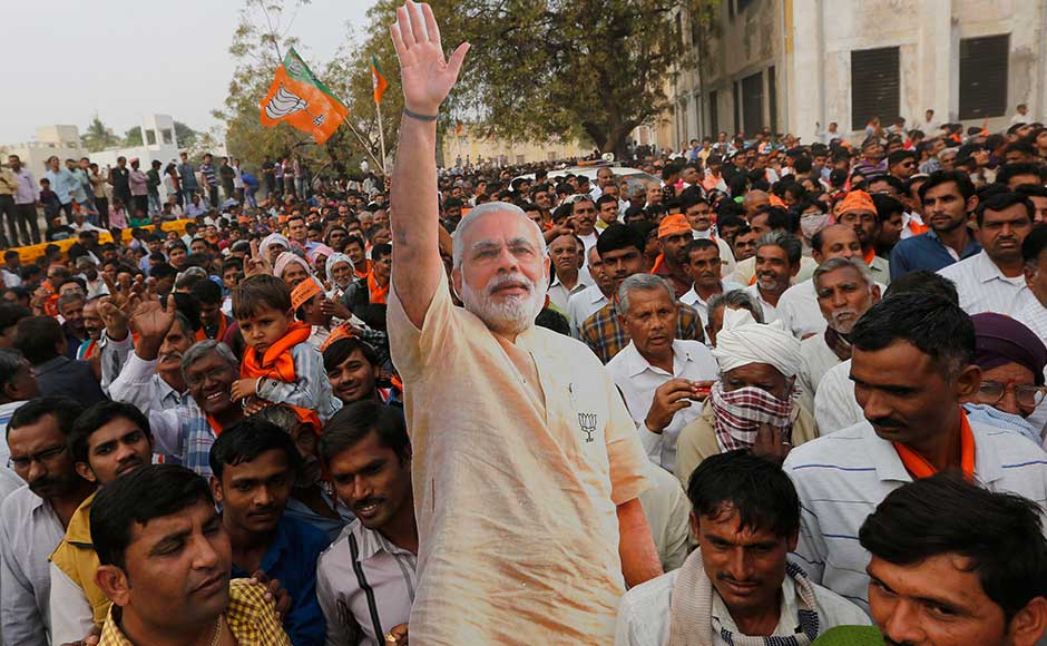 On Monday, the prime minister will be holding public meetings at Valsad, Bhavnagar and Saurashtra. Gujarat will vote in two phases — on 9 and 14 December — to elect a 182-member Assembly. BJP supporters carry a cutout of Modi after a rally in Surendranagar. AP