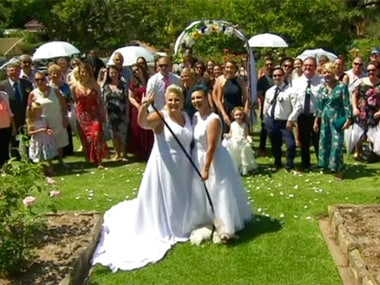 newlywed couple, Amy Laker, center left, and Lauren Price, center right, pose for a photo during their ceremony in Sydney. AP