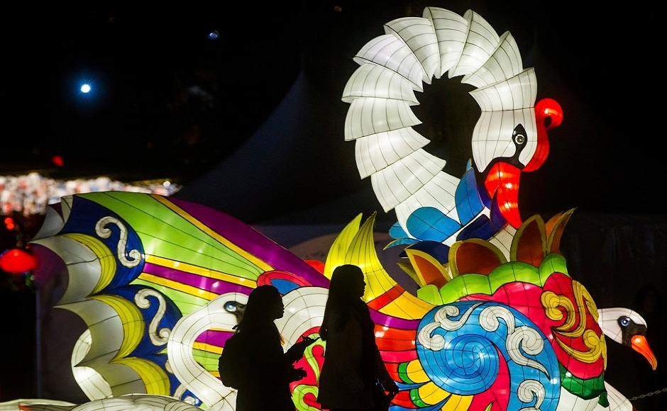 Two young women walk past a swan lantern during the opening night of the Vancouver Chinese Lantern Festival at the Pacific National Exhibition, in Vancouver, British Columbia. The festival features hundreds of illuminated lanterns. AP