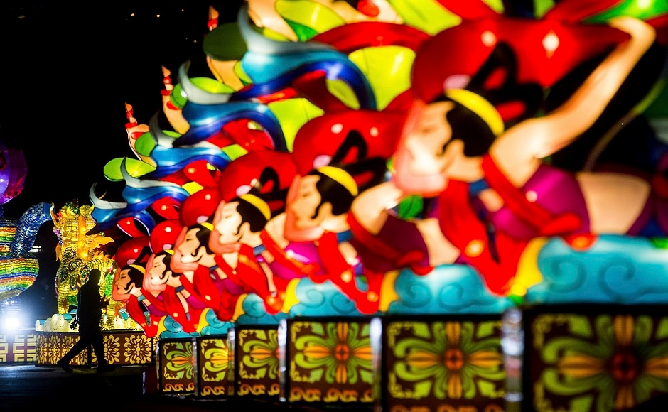 A man is silhouetted while walking past a row of lanterns during the opening night of the Vancouver Chinese Lantern Festival at the Pacific National Exhibition, in Vancouver, British Columbia. AP