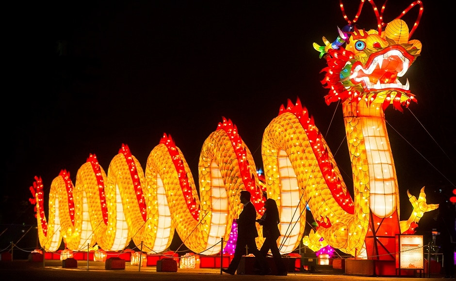 People walk past a dragon during the opening night of the Vancouver Chinese Lantern Festival at the Pacific National Exhibition, in Vancouver, British Columbia. AP