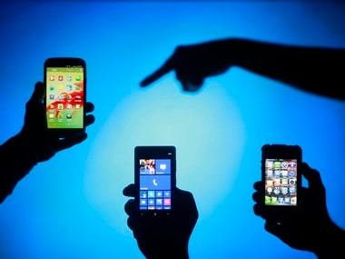 Men pose with Samsung Galaxy S3 Nokia Lumia 820 and iPhone 4 smartphones in photo illustration in Zenica