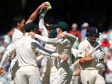 Australian teammates celebrate the second Test win as England's Jonny Bairstow walks away at the end of the Adelaide game. AP