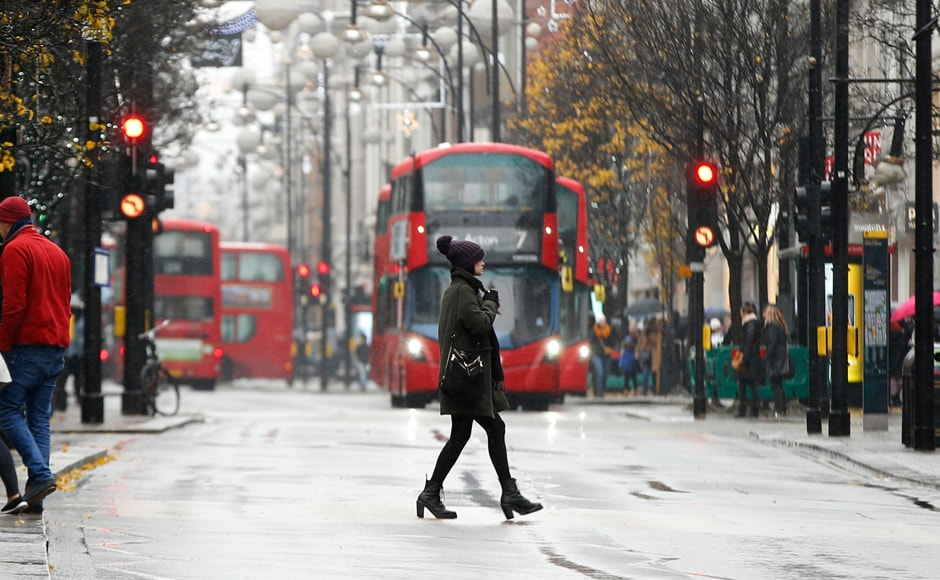 Snow falls as a woman crosses Oxford Street in London. The heaviest snowfall in four years in Britain caused travel mayhem on Sunday, while more than 300 flights were cancelled at Germany's busiest airport as several parts of Europe remained covered with snow. AP