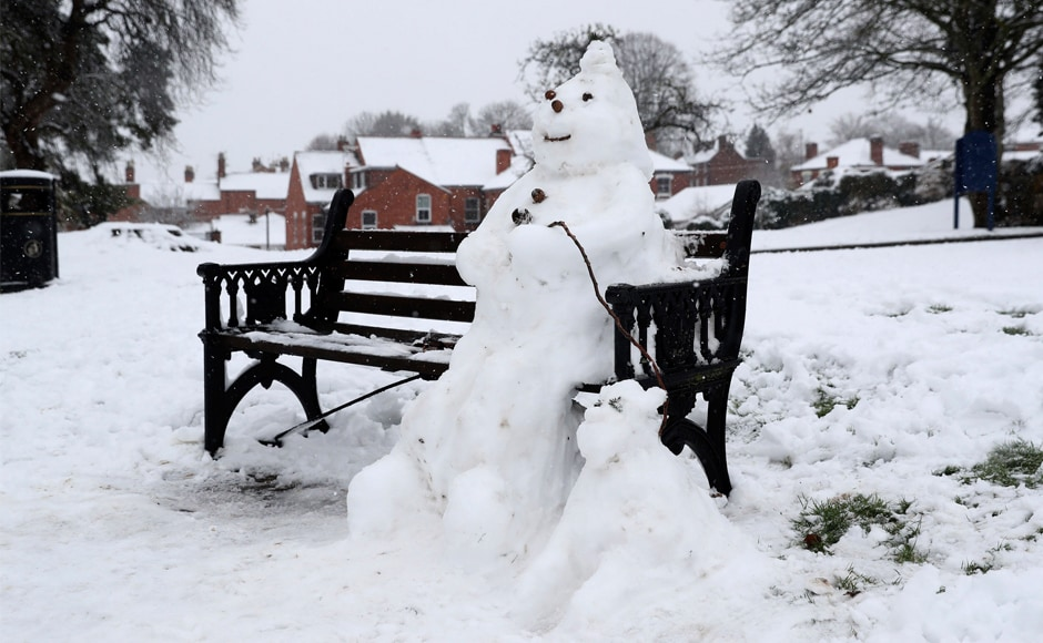 A snowman and dog on a bench in Worcester, England. Police forces in worst-hit Wales and central England urged motorists not to travel unless